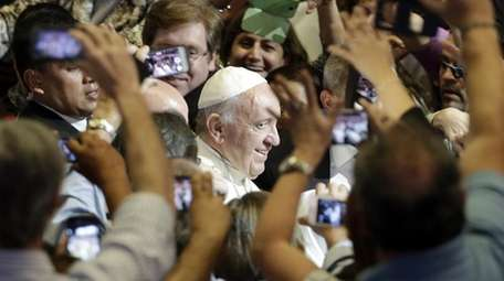 Pope Francis is surrounded by people taking pictures