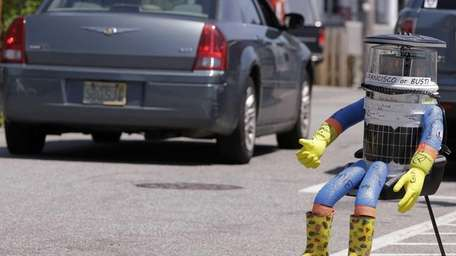 A car drives by HitchBOT, a hitchhiking robot