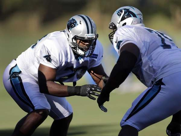 The Carolina Panthers' Michael Oher, left, squares off