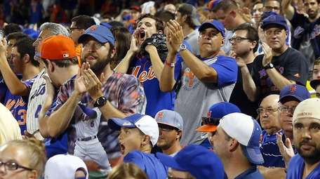 New York Mets fans cheer after the seventh