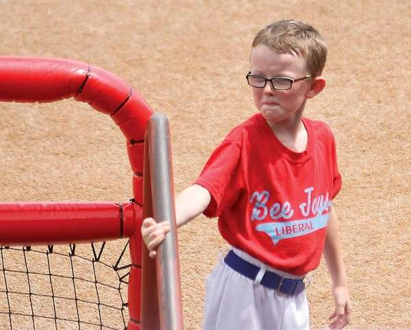Bat boy Kaiser Carlile, 9, gets ready for