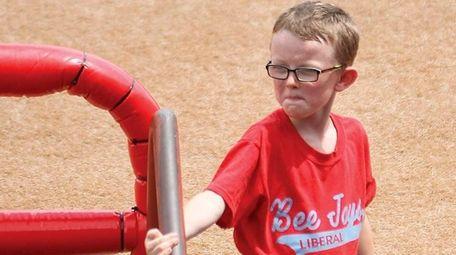 Bat boy Kaiser Carlile, 9, gets ready for
