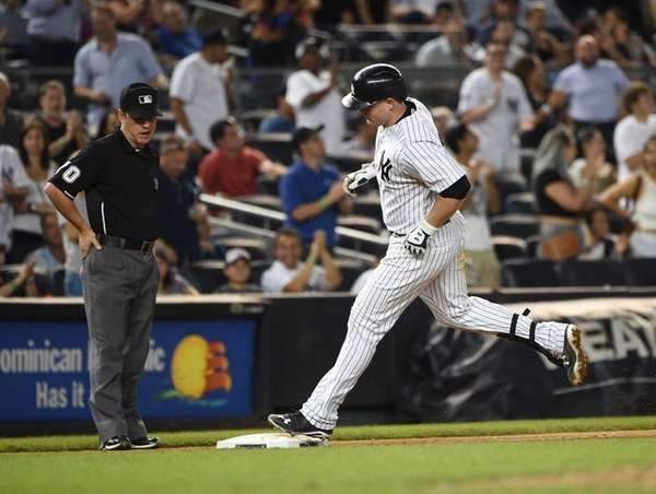 Yankees catcher Brian McCann rounds third base on