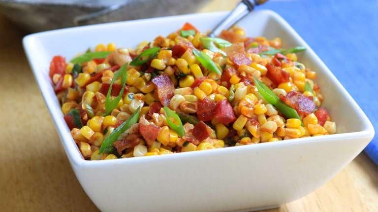 Corn and tomatoes are cooked in a skillet