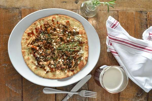 Sweet thyme flatbread topped with sweet sausage, fresh