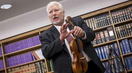 Violin maker and appraiser Phillip Injeian holds a