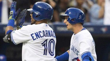 The Toronto Blue Jays' Edwin Encarnacion, left, is