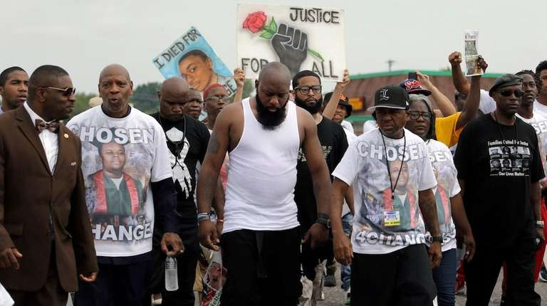 Michael Brown Sr., center, takes part in a