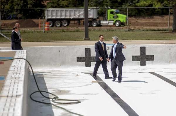 Officials tour the drained swimming pool at Roberto
