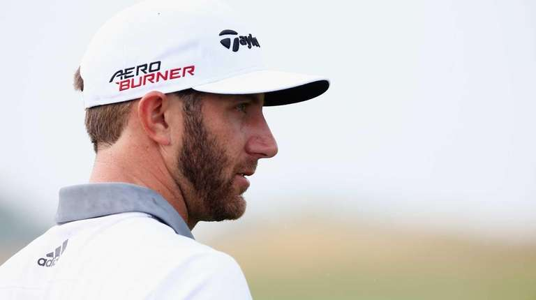 Dustin Johnson waits on the practice ground during