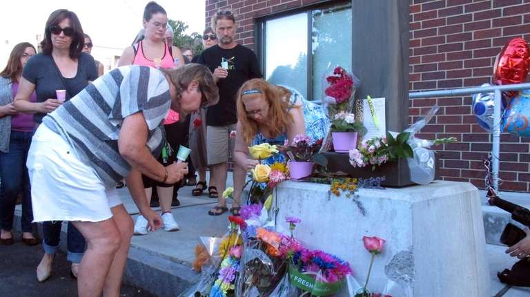 People place flowers, Sunday, Aug. 9, 2015, at