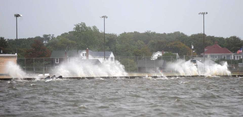 Waves crash over the dock at Shorefront Park