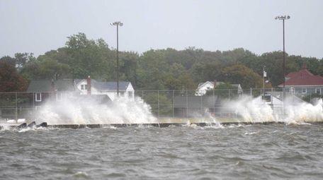 Waves crash over the dock at Shorefront Park