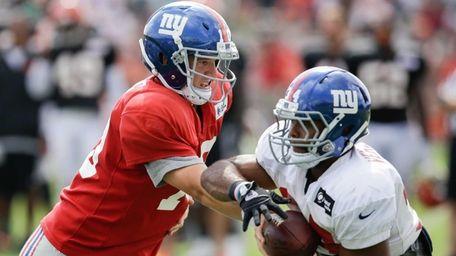 New York Giants quarterback Eli Manning, left, hands