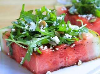 Grilled watermelon steaks topped with arugula, feta and