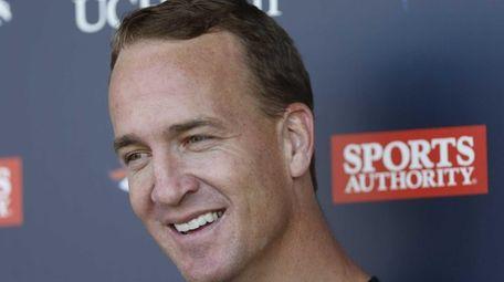 Denver Broncos quarterback Peyton Manning jokes with reporters