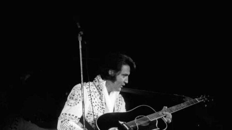 Elvis Presley on stage performing at the Nassau