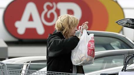 A shopper loads groceries into her car in