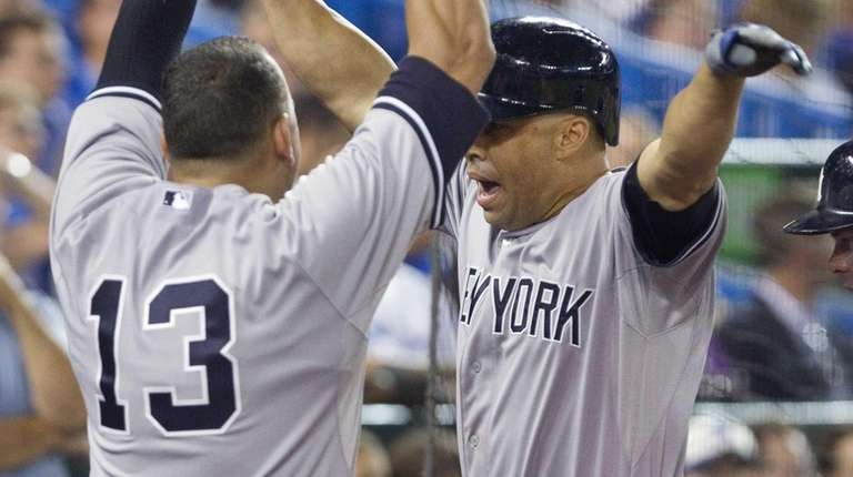 New York Yankees' Carlos Beltran, right, is greeted