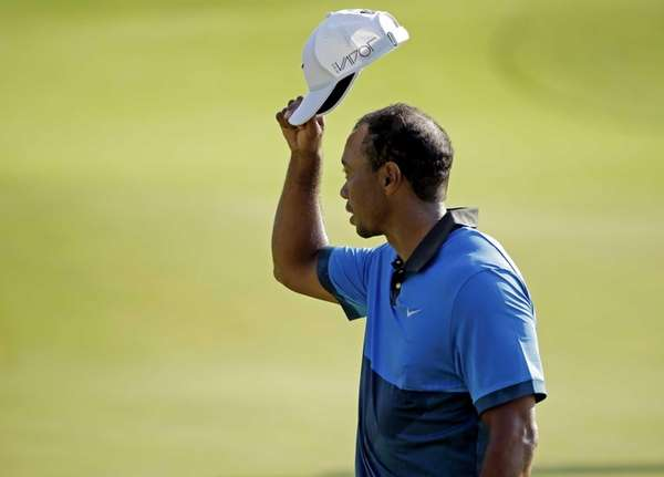 Tiger Woods tips his hat to the crowd