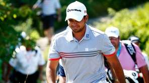 Jason Day of Australia walks to the first