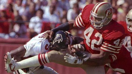 San Francisco 49ers defensive back Ronnie Lott tackles