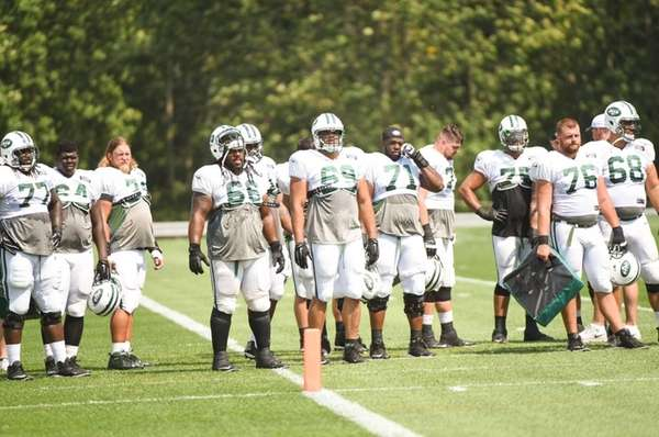 New York Jets offensive linemen look on during