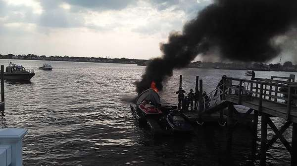 Firefighters battle a fire on a boat docked