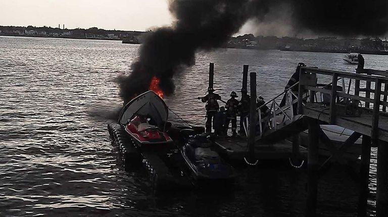 Firefighters battle a fire on a boat docked