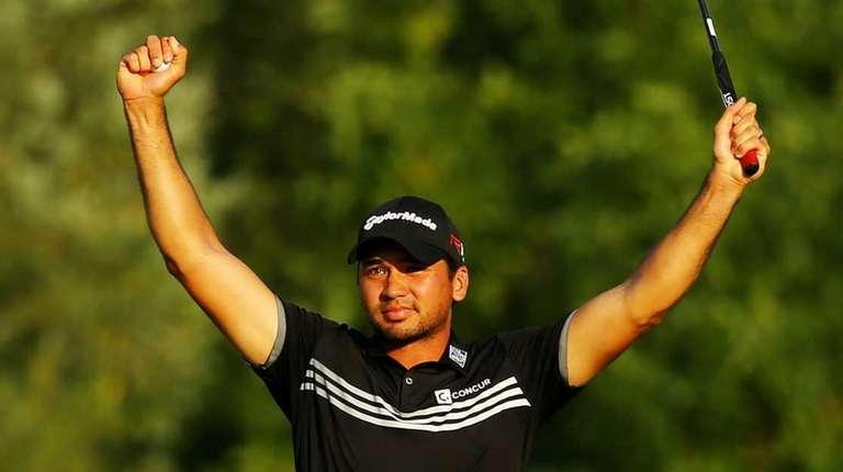 Jason Day celebrates on the 18th green after