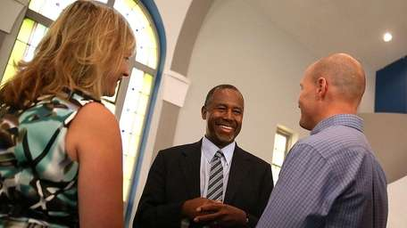 Republican presidential hopeful Ben Carson greets parishoners during
