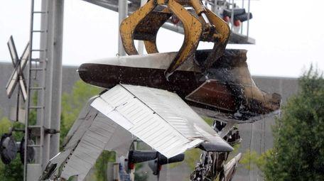 A LIRR crane picks up wreckage of plane