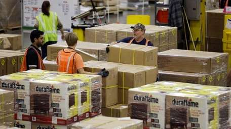 Workers move merchandise at the Amazon fulfillment center