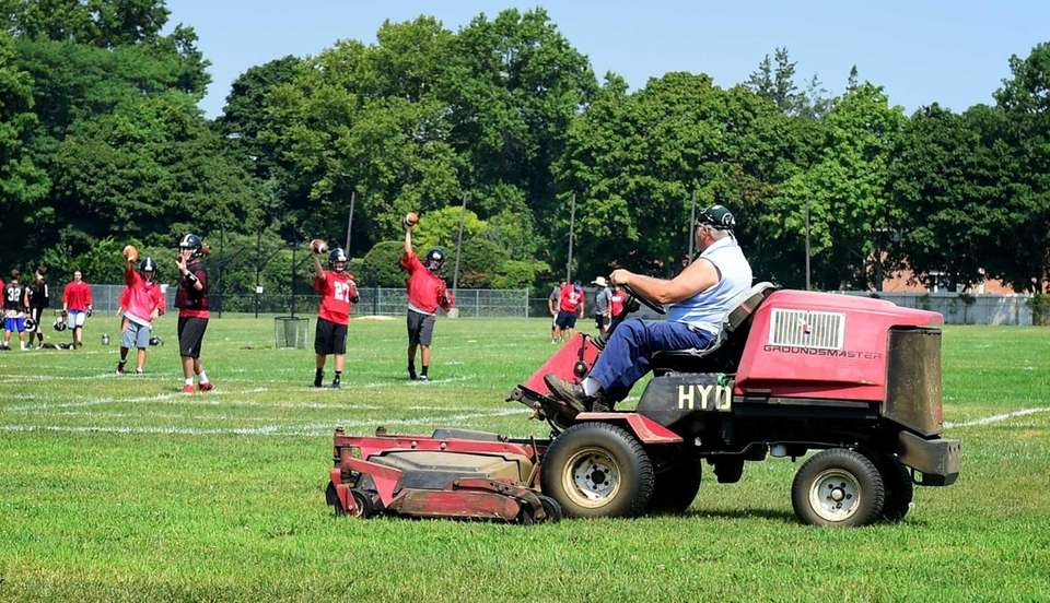 A groundskeeper mows the grass while members of