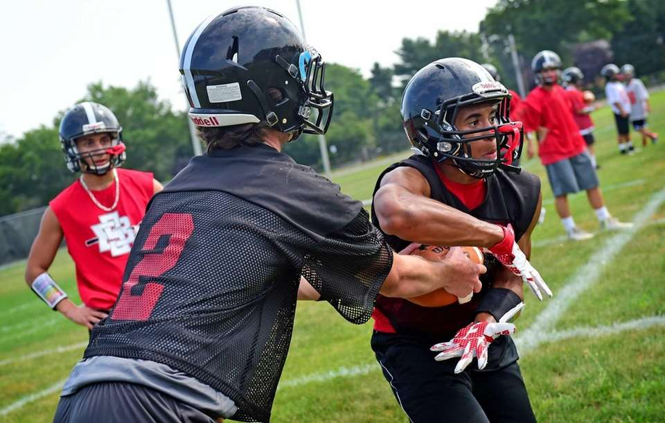 Syosset's Will Hogan, left, hands the ball off