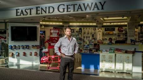 Bryan DeLuca stands in front of his shop,