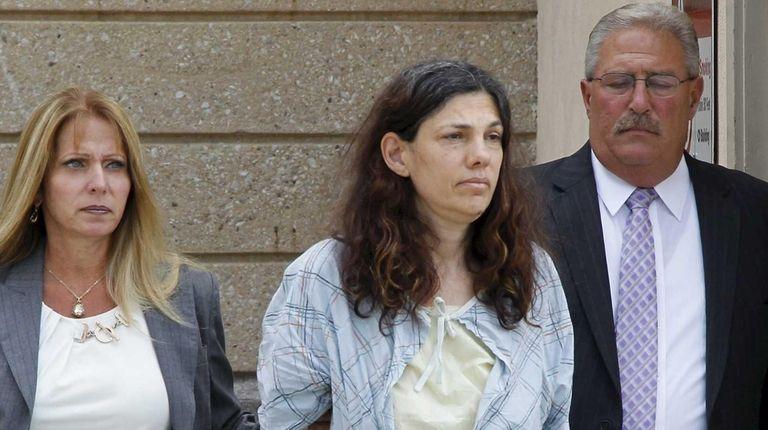 Suzan Grossman-Kerner, 56, of Oceanside, is escorted out