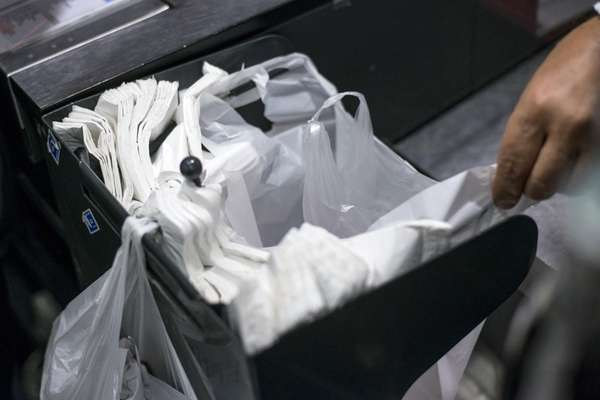 A person picks up a plastic bag on