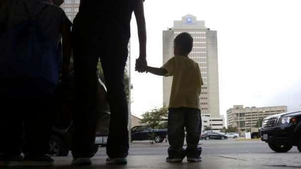 A young boy holds hands with his mother