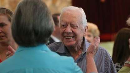 Former President Jimmy Carter reaches to embrace his