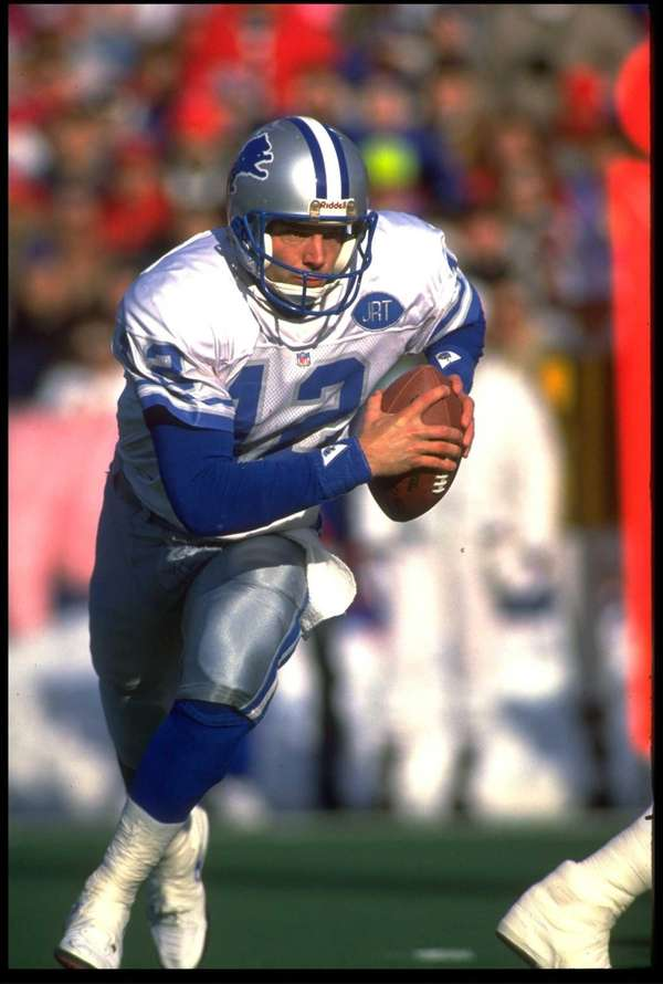 Detroit Lions quarterback Erik Kramer scrambles away from