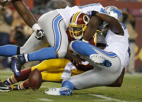 Washington Redskins quarterback Robert Griffin III fumbles the