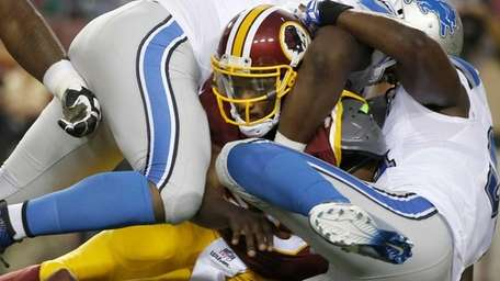 Washington Redskins quarterback Robert Griffin III fumbles the
