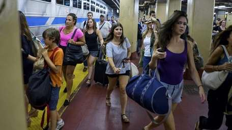 Passengers at Penn Station prepare to board the