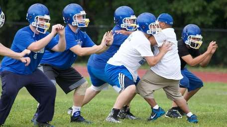 Riverhead High School football players work out during