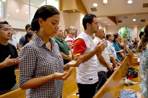 Parishioners raise hands in prayer during the Spanish-language