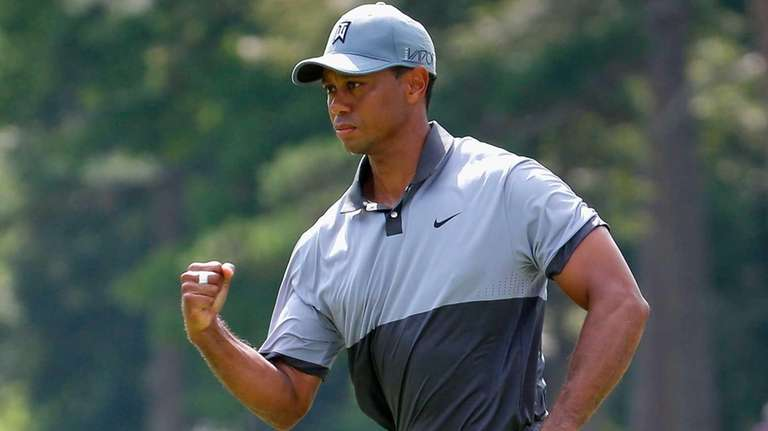 Tiger Woods reacts after making his par putt