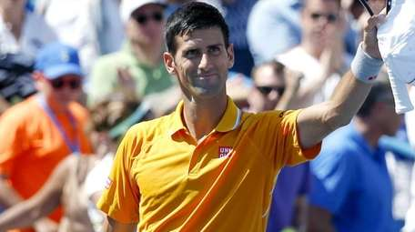 Novak Djokovic waves to the crowd after defeating