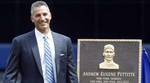 Andy Pettitte stands next to his Monument Park