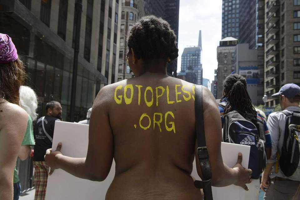 Participants, some topless, march in midtown Manhattan during